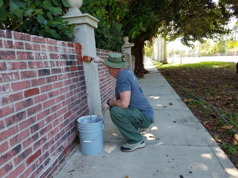 Mr. Paul Amato volunteers to paint a brick wall on 184th street.
