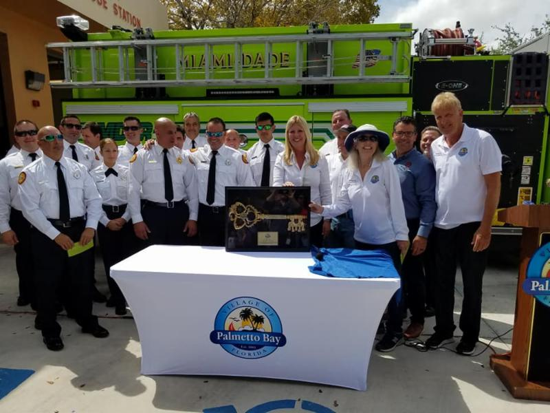 Photo of Mayor, Council and Firefighters gathered around a large key to the city presented to Fire Station number 50 on April 8, 2019