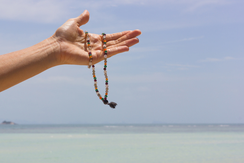 Mala beads necklace hanging from a woman s hand with the sea and the sky on the background. Summer souvenir concept