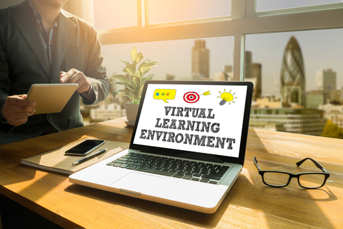 VIRTUAL LEARNING ENVIRONMENT Thoughtful male person looking to the digital tablet screen_ laptop screen_Silhouette and filter sun
