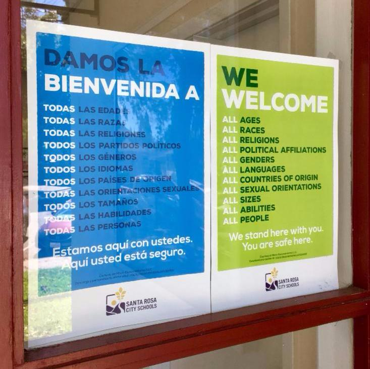 We Welcome posters in a window