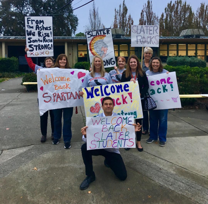 Slater MS staff hold welcome back signs after fires