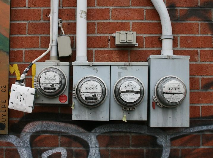 Photograph of four electricity meters outside of a brick building. Photograph by Nicolas Nova, Creative Commons license.
