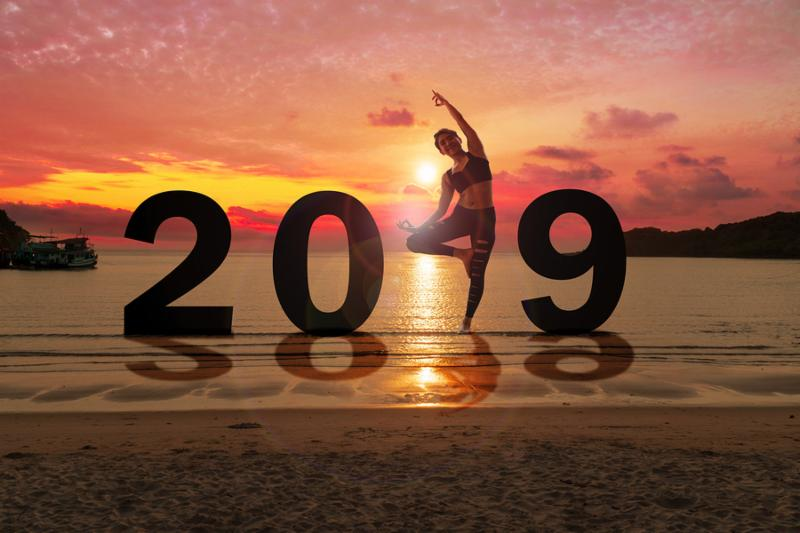 Greeting card 2019 happy new years. Silhouette of healthy young woman practicing yoga on tropical beach with sky sunset. People doing yoga standing between numbers 2019. concept celebrating new year.