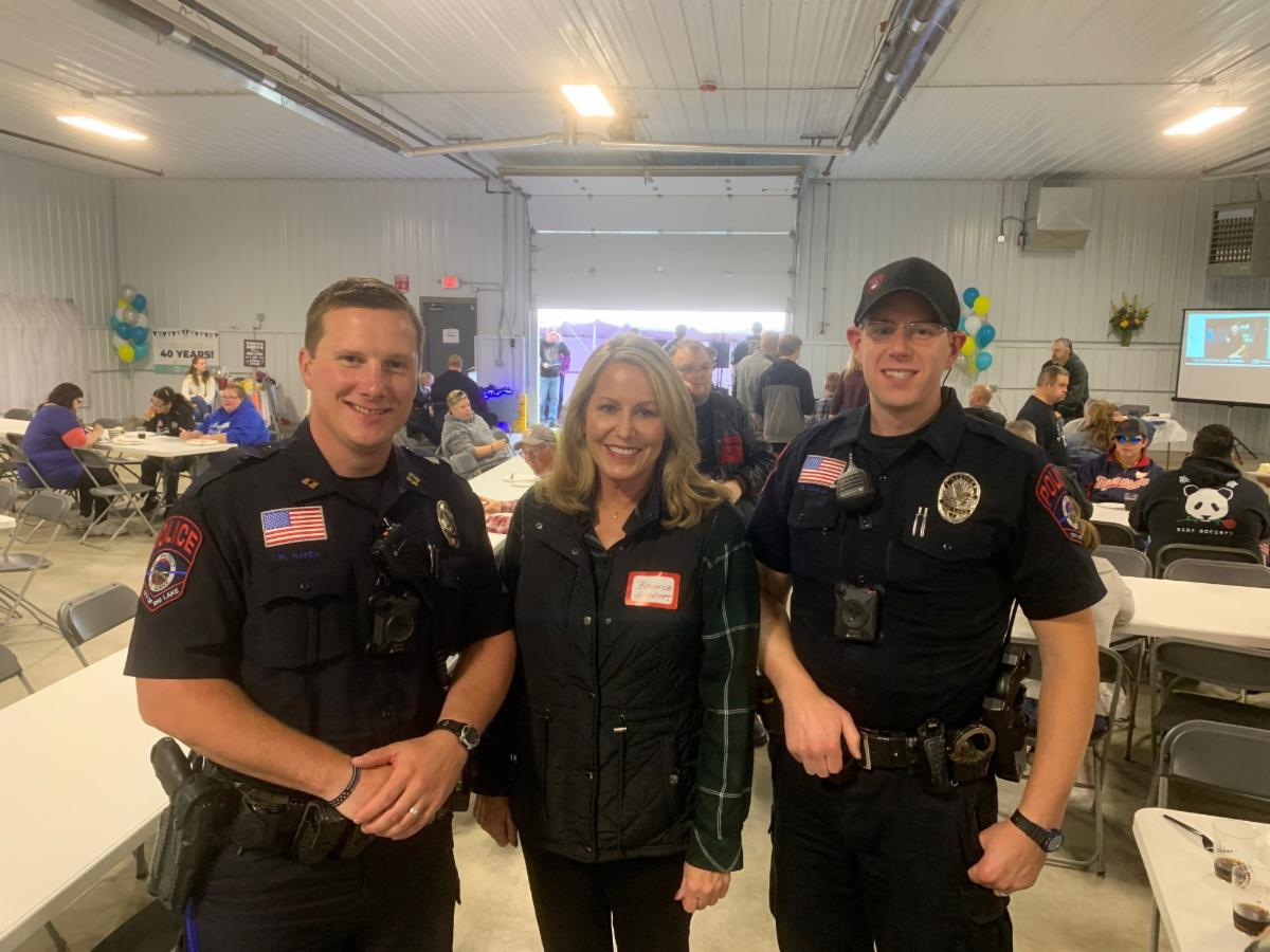 Options, Inc. Executive Director Brenda Geldert visits with local police at the nonprofit's 40th anniversary celebration