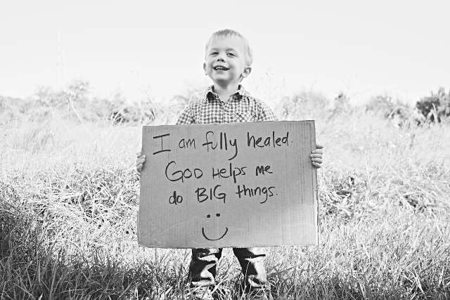 young boy holding cardboard sign reads I am healed!