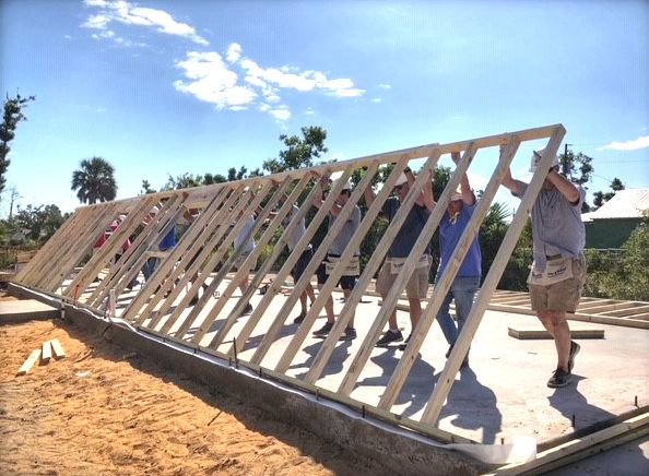 Clergy raising the wall of a Habitat for Humanity home build.