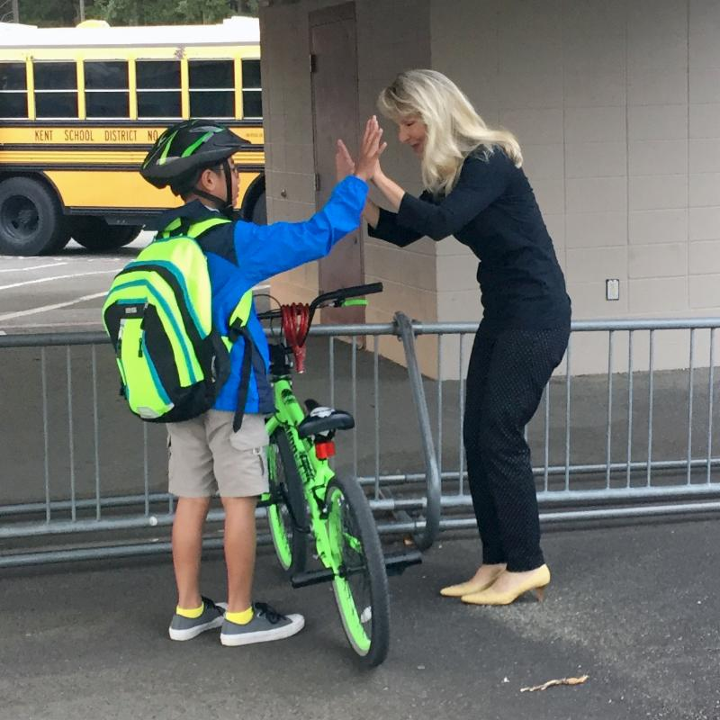 Elementary student on bike giving a high 5 to the school counselor