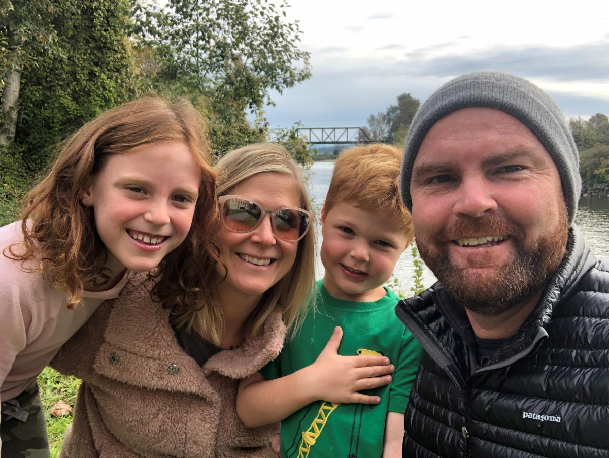 Dana with her husband and two children in front of trees and a bridge