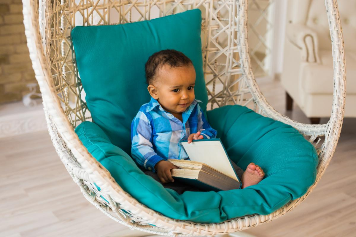 Toddler sitting in a wicker chair flipping through a book