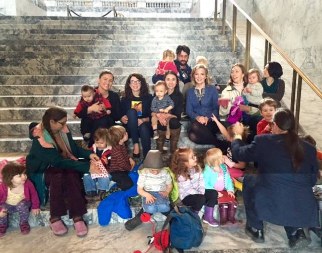 A gathering of parents and advocates sitting on the steps outside of the legislative building in Olympia Washington