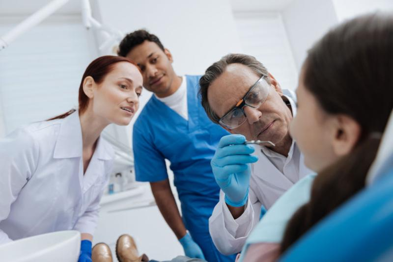 A male and female student both watch on as a dentist examines a young girl's mouth.