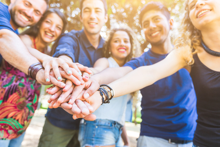Group of smiling adults standing around in a circle with hands on top of each other in solidarity.