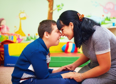 profile of loving mother touching foreheads with her son with a disability, both are smiling