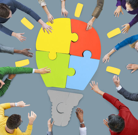 Image from bird's eye view looking down on a group of people in a circle putting together puzzle pieces to form a multicolored lightbulb