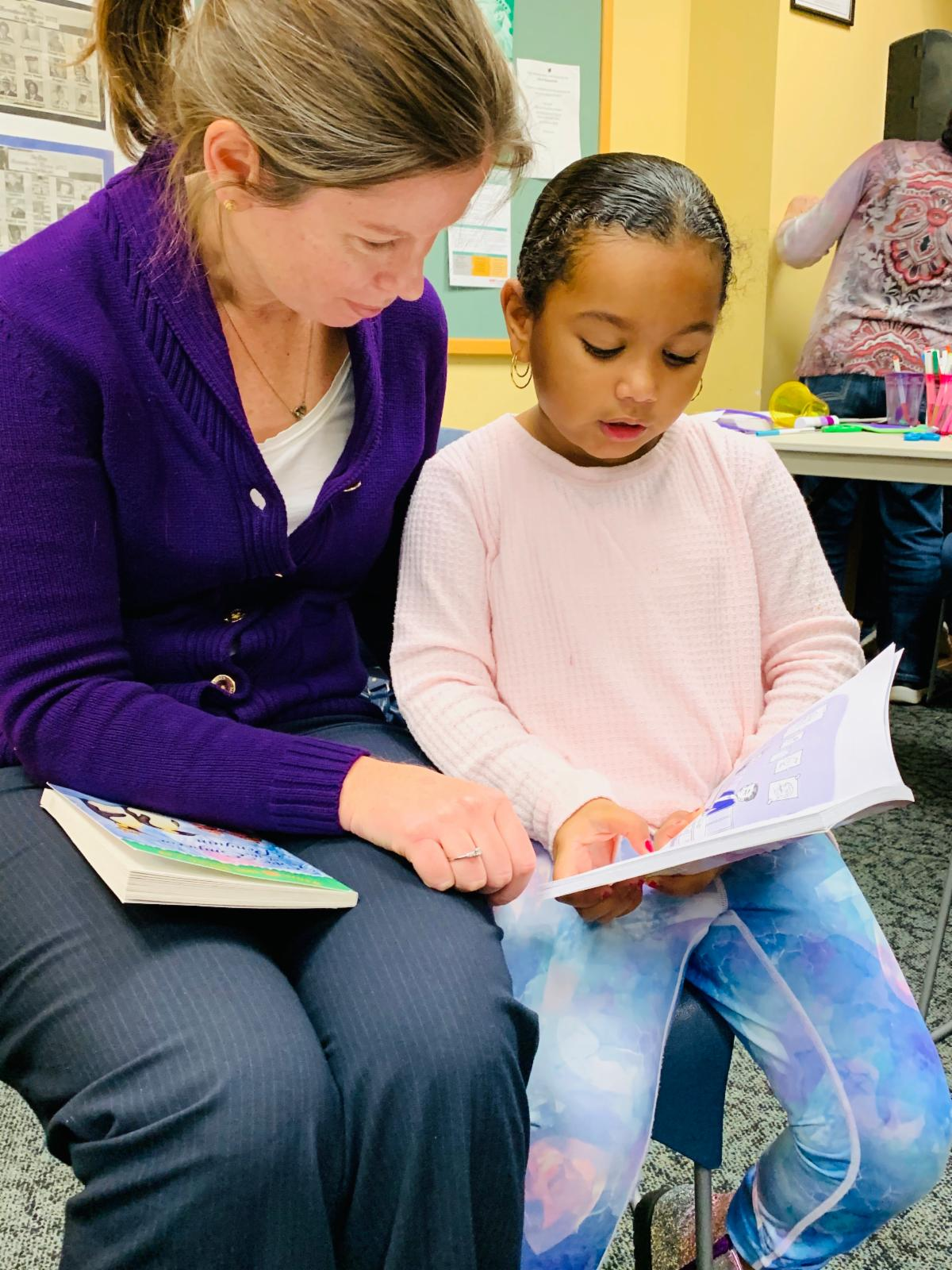 a picture of a little girl reading a book with an adult