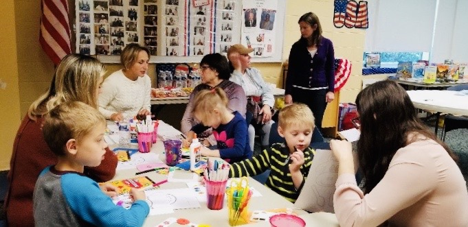 a picture of children and adults engaged in a craft activity together