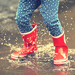 Child_s rubber boots-clad legs jumping in a puddle