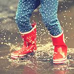 Botas de lluvia infantiles salpicando en un charco