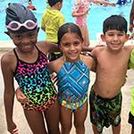 Ni_os sonrientes en traje de ba_o alrededor de una piscina