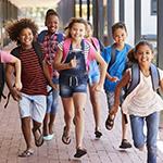 Happy children running through a school hallway.