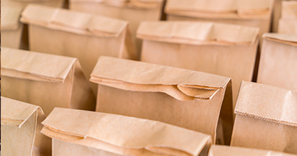 Rows of school lunches in brown bags.