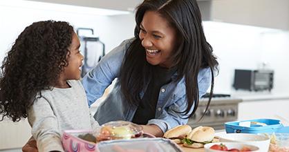 Una mamá y su hija preparan juntas el almuerzo escolar.
