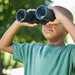 Little boy looking through binoculars.