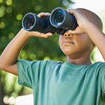 Ni_o mirando a trav_s de binoculares.