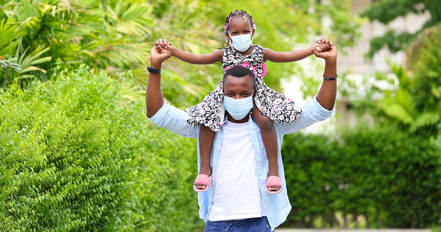 Yon timoun Afriken Ameriken chita anlè zepòl papa li. Pa Akarawut/stock.adobe.com