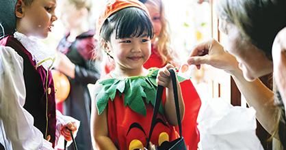 Una niña pequeña disfrazada de calabaza recibe caramelos en Halloween