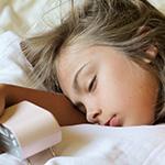 Una ni_a peque_a en la cama_ sosteniendo un despertador.