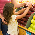 Madre ayudando a su hija a escoger frutas en el mercado