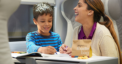 A boy and his mother enjoy activities aboard a Brightline train.