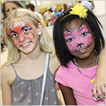 Two smiling young girls with painted faces_ one a demon and one a cat_ at the Family Expo.
