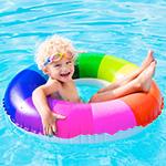 Un ni_o flota feliz en una piscina sobre un salvavidas a rayas de arco iris.