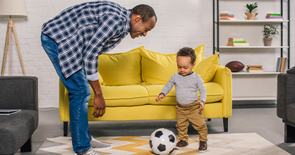 A father and son practice soccer inside the home.