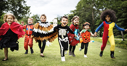 Niños que corren en disfraces de Halloween