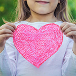 Young girl holding up a paper valentine heart.
