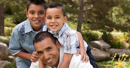 Papá e hijos felices al aire libre.