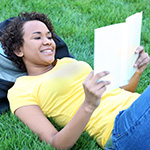 Teen girl happily reading a book.