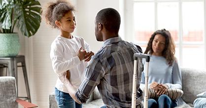 Papá que se va habla con su hija mientras la mamá los mira.