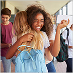 High school students happily hugging each other_ with acceptance letters in their hands
