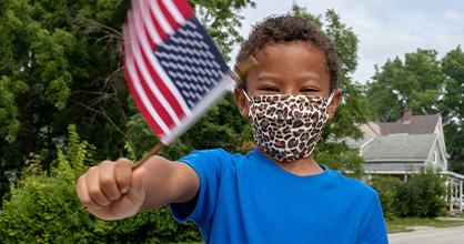Un niño ondea una bandera estadounidense con una máscara puesta.