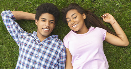 A teenage boy and girl enjoy each other's company laying in the grass.