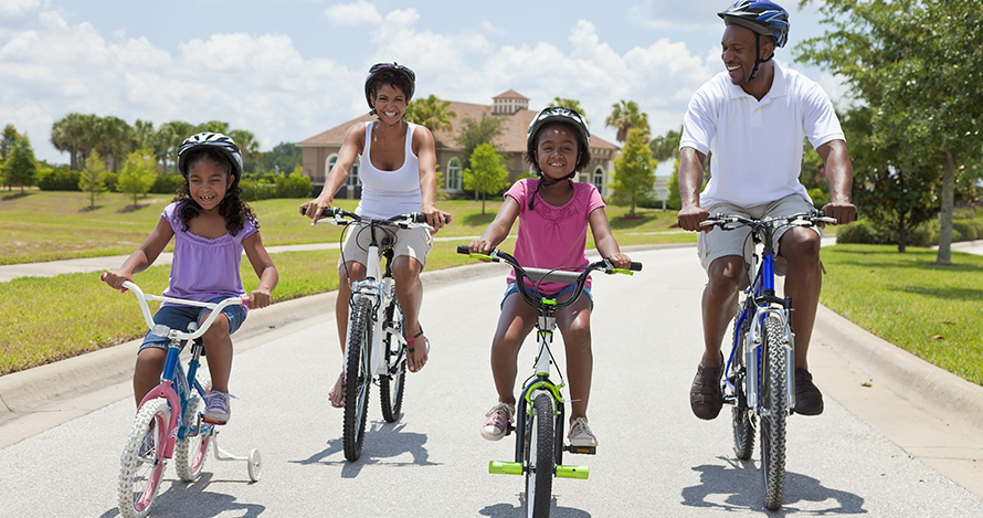 An African American family enjoys a bike ride during the summer.