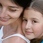 Madre sonriente siendo abrazada por su joven hija