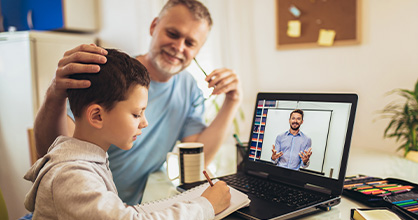 Un padre ayuda a su hijo con sus estudios virtuales.