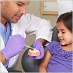 Dentista le muestra a una ni_a c_mo cepillarse los dientes