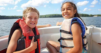Niños contentos con salvavidas en un bote.